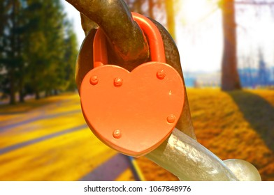 A red heart shaped lock in the sunlight. Sunny day in park on the background.