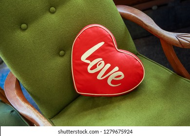 Red heart shaped pillow that says love, on a vintage green chair