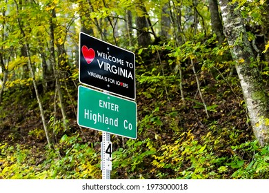 Red heart sign on highway in Virginia with welcome to state sign and is for lovers text logo in Highland county, VA by mountain forest with fog