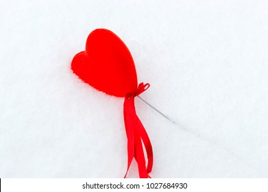 Red heart in snow. Love concept. Valentine day in winter.