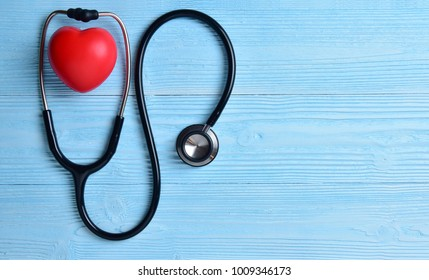 Red heart with stethoscope on blue wooden background. Copy space. Valentines day.