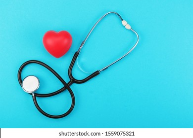 Red heart and stethoscope on a blue background. Health care concept, health worker, heart health care, medical care. Layout with a copy space for your text. Flat layout, top view.