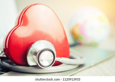 Red heart with stethoscope on notebook computer desk with blur global model, health insurance for medical in world wide concepts