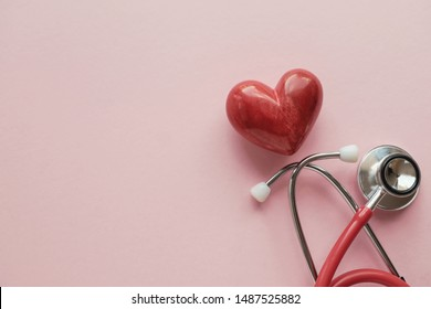 Red heart with stethoscope on pink background, heart health,  health insurance concept, World heart day, world health day