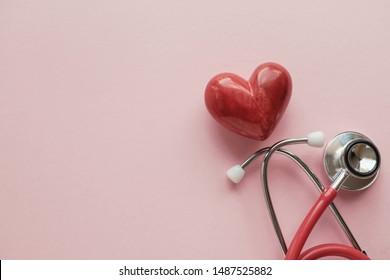 Rotes Herz mit Stethoskop auf rosafarbenem Hintergrund, Herzkrankheit, Krankenversicherung Konzept, Weltherztag, Weltgesundheitstag, Arzt-Tag