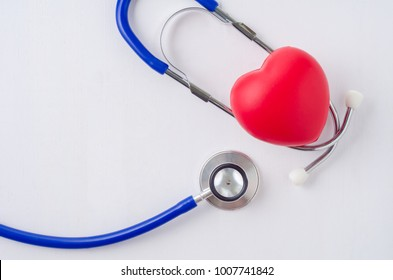 Red heart with stethoscope on white wooden background.