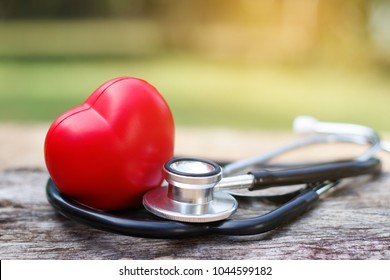 Red heart and a stethoscope on wooden background.