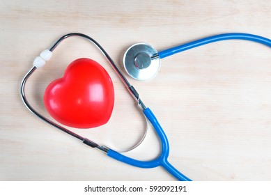 Red heart with stethoscope on wooden background, healthcare
