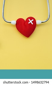 Red heart with stethoscope on yellow background