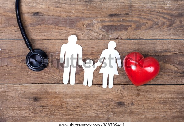 Red heart, stethoscope and paper man Family on wooden table