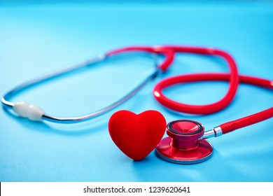 Red heart and stethoscope or phonendoscope on on blue background.Selective focus.