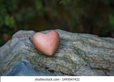 Red heart stone on a marble pedestal