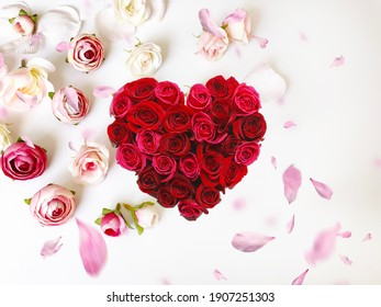 Red Heart  symbol on  pink roses flower petal on white  festive floral background