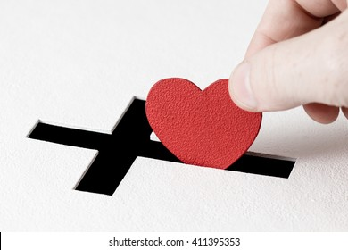 Red heart symbol is put by person's hand into slot of white donation box, slot is shaped like Christian cross. Concept of sincere devotion to faith with whole heart. Close-up shot