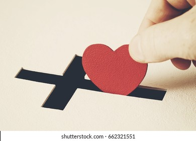 Red heart symbol is put by person's hand into slot of white donation box, slot is shaped like Christian cross. Concept of sincere devotion to faith with whole heart. Close-up shot, tinted effect