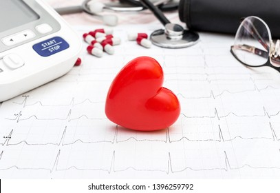 Red heart with tonometer and stethoscope on cardiogram. Medical concept.