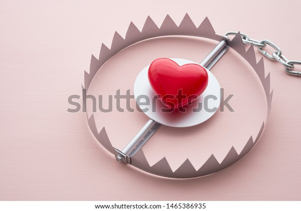 Red heart in a trap on pink background. Online internet romance scam or valentine day in darkside concept. Love is bait or victim.