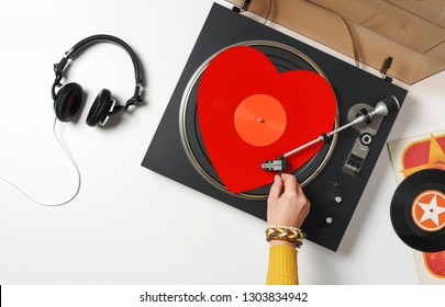 A red heart vinyl record turntable on a white table with plates. Included gramophone, black headphones. The hand of a girl DJ with bright accessory puts a stylus on a vinyl record. Valentine's Day