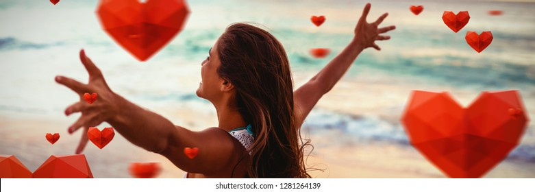 Red heart with white blackground against side view of woman stretching out her arms