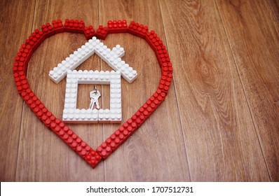 red heart with a white house and a bunch of keys inside laid out of bricks or blocks of children's constructor close-up on a wooden background. Copy space, space for text.