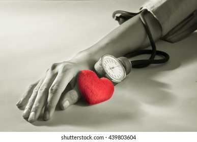 Red heart with woman arm checking blood pressure.
