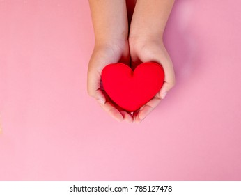 red heart in woman hand on pink background