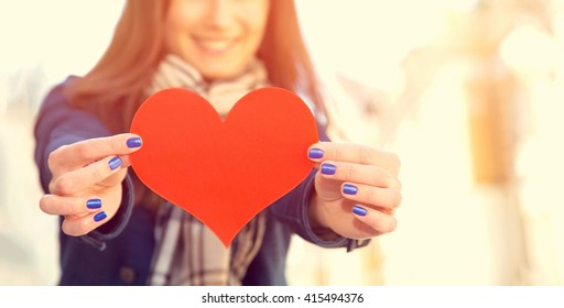 Red heart in the woman hands, close up. Love symbol young happy woman hold. Blurred people.
