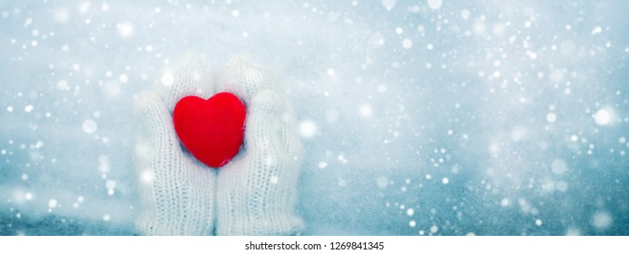 Red heart in woman's hands wearing white woolen mittens. Top view snow background. Valentine's Day concept. Web banner format