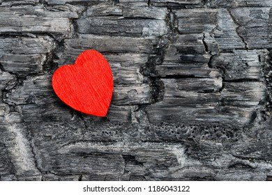 Red heart wood lies on black burnt Board, the concept of loneliness, pain, suffering,