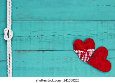 Red hearts border and white rope with knot on blank antique teal blue old weathered background