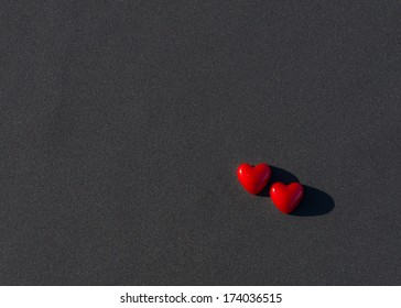 Red hearts on ice covered by coal dust