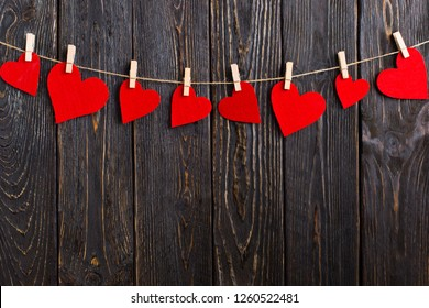 Red hearts on rope with clothespins, on black wooden background. Place for text, copy space.