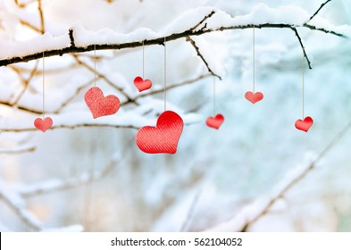 Red hearts on snowy tree branch in winter. Holidays happy valentines day celebration heart love concept. Six hearts.