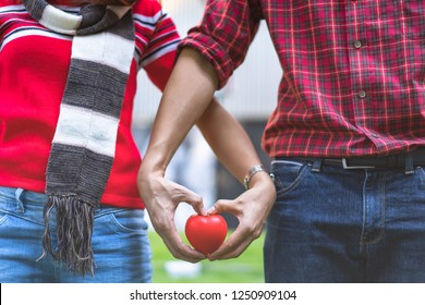 Red hearts placed in the hands of couples who warmly hold hands as a symbol of love, togetherness, winter with love, valentine day,Sweetheart's Romantic Holiday.