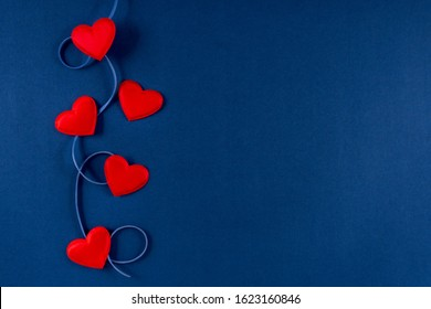 Red hearts with ribbon on classic blue 2020 color background. Valentines day 14 february concept. Flat lay, copy space, top view, banner