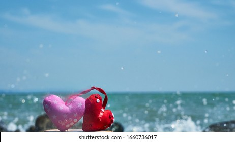 Red hearts. Soft toy. Handwork. Sea shore. Waves hit the stones.