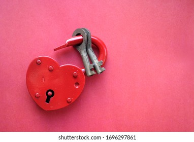 red heart-shaped lock on a red background with keys