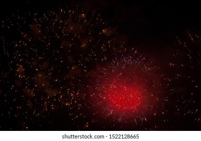 red heart-shaped sparks of salute, orange, neon and golden sparks of fireworks in the sky and smoke from charges