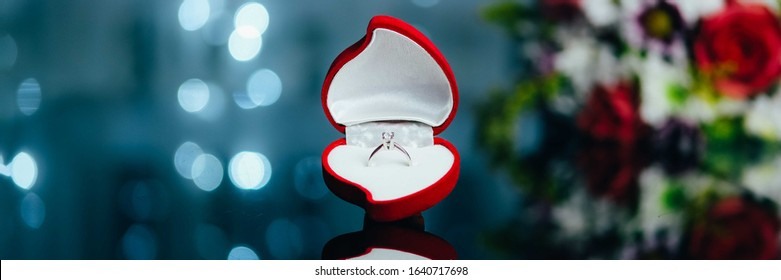 Red heart-shaped velvet box with engagement diamond ring on background with bokeh lights and flowers. Valentine background. Presents for woman on Valentine's Day. Love, proposal concept. Web banner.
