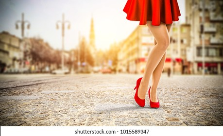 Red heels and slim woman legs with red sexy dress in city.
