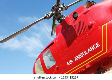 Red helicopter of air ambulance isolated on blue sky background. Detail of the helicopter blades. Cornwall, UK