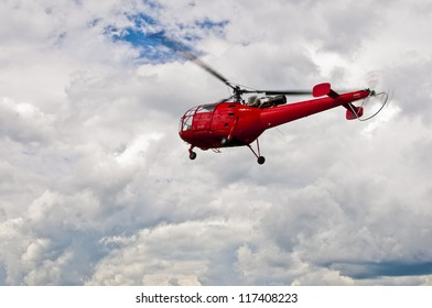 Red Helicopter in a Cloudy Sky