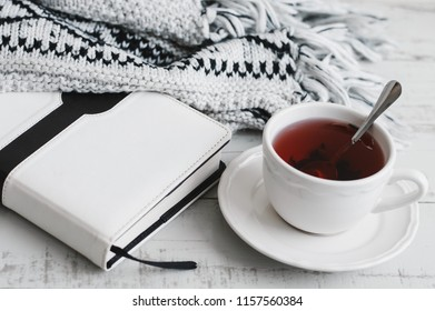 Red hibiscus tea, book and knitted blanket on wooden table. Cosy atmosphere. Tea break