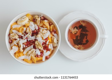 Red Hibiscus tea and fruit salad with mango, coconut flakes, walnut, tangerine, dried apricot, banana and pomegranate seeds on white table, top view