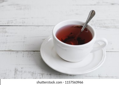 Red hibiscus tea in a small white cup with a metal spoon on wooden background. Tea break