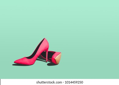 Red high heels isolated on a bright green pastel background. Fashion concept, catwalk. A modern and fashionable shoe store.