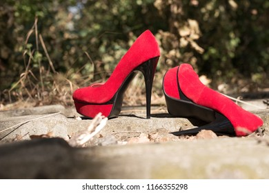 Red high heels of a missing unknown woman in the forest