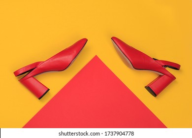Red high heels women shoes. High fashion luxury female footwear. Creative flat lat top view design concept on colorful background.