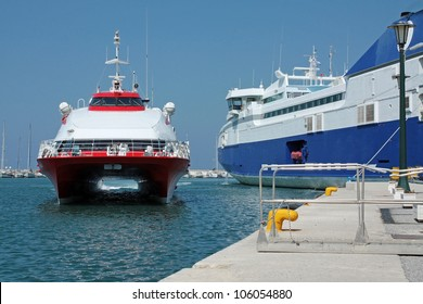 A red high speed boat arrives at the port of an island in Greece