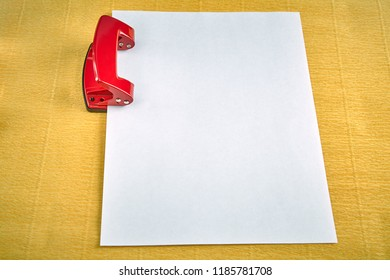 Red hole puncher with empty sheet of paper, yellow background.